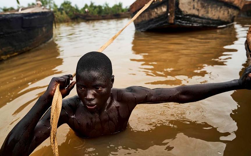 Um escavador do Mali puxa seu barco para um local onde pode mergulhar e recolher a areia do leito do rio Níger perto de Kangaba, no sudoeste da região de Koulikoro.