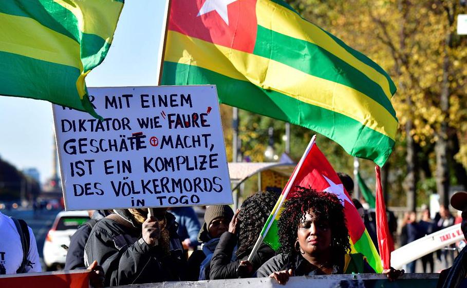 """Protestos em Berlim no local onde se realiza o Congressos de AXICA, onde se discute o projeto chamado """"Um Pacto com a África"""". Para os manifestantes, """"quem faz negócios com um ditador como Faure é cúmplice do genocídio no Togo""""."""