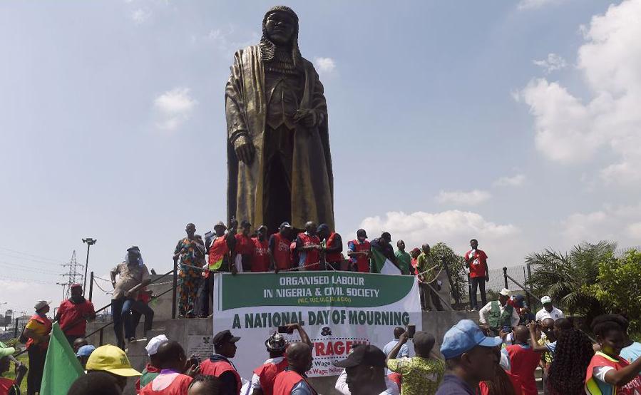 Os trabalhadores se reúnem em torno da estátua de crítico social nigeriano e político Gani Fawehinmi durante uma marcha de protesto contra o fracasso do governo chegar a acordo sobre um novo salário mínimo, em Lagos.