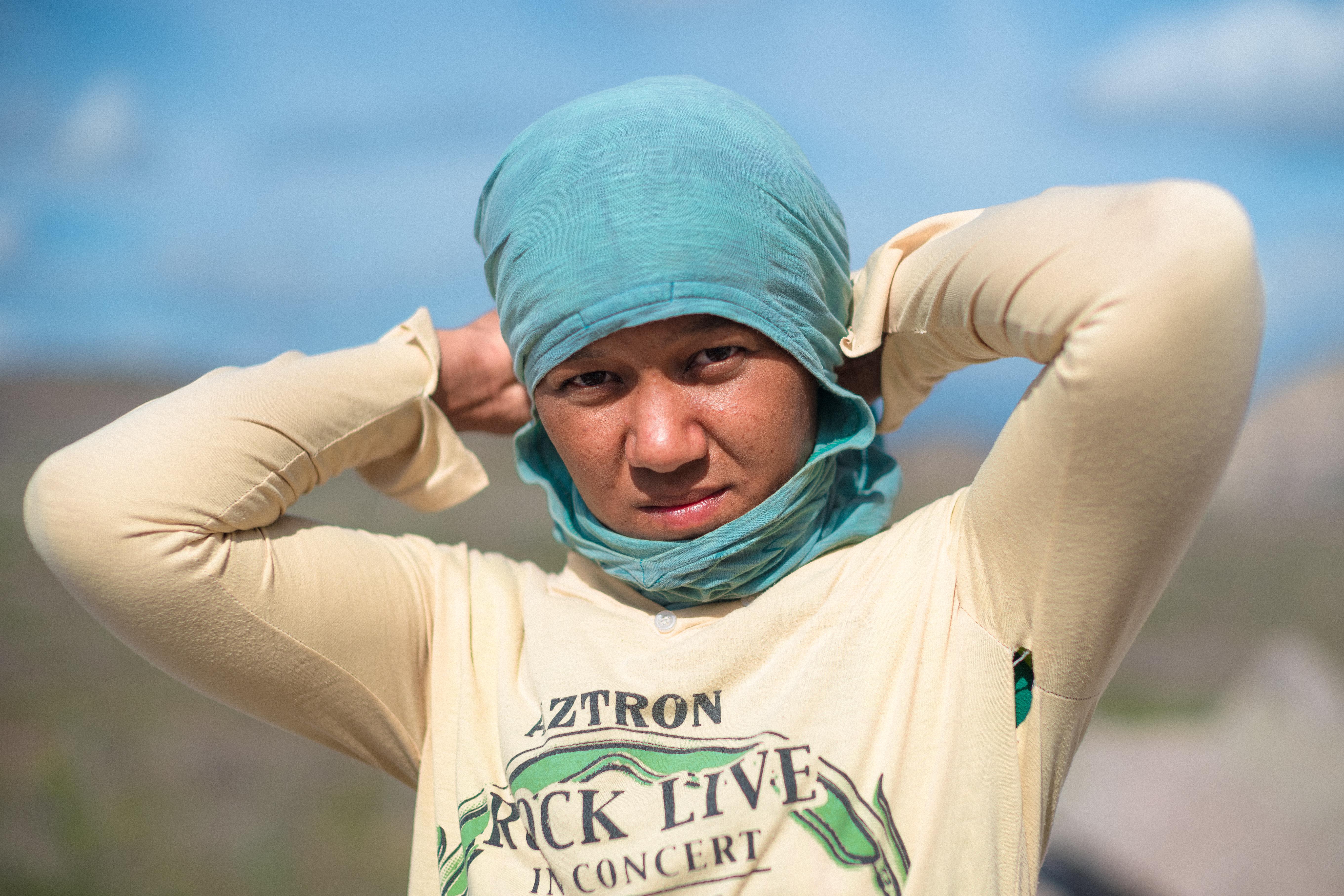 Com camisas no rosto, elas trabalham no sol quente para se sustentar