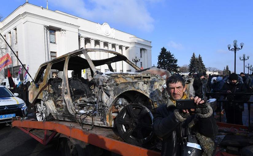 Um ativista do movimento AutoEuroSyla  faz uma foto ao lado de um carro de luxo queimado durante protestos em Kiev, a favor da redução de taxa de imposto especial de consumo sobre carros usados.