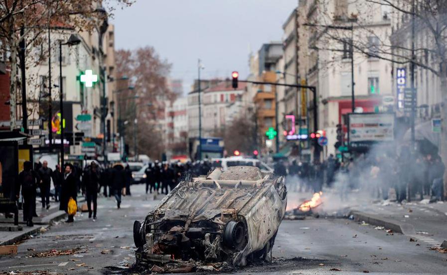Carro queimado em frente à escola Lycée Professionnel Jean-Pierre Timbaud após ser incendiado por estudantes em protesto contra as reformas educacionais propostas pelo governo francês em  Aubervilliers, subúrbio de Paris.