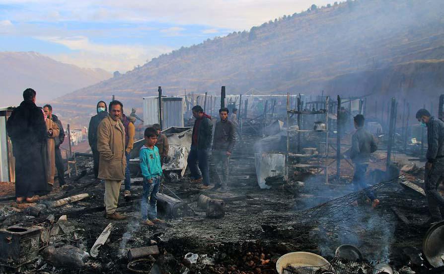 Refugiados sírios observam os danos de um incêndio que atingiu o acampamento de refugiados na aldeia de Yammouneh, no vale de Bekaa, no Líbano.