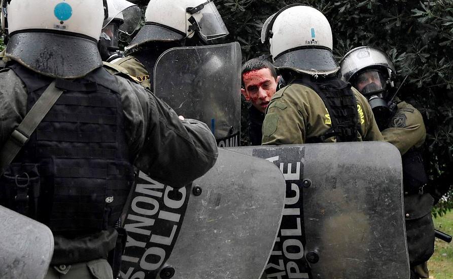Polícia detém um manifestante após confrontos em uma manifestação em Atenas em lembrança do 10º aniversário da morte de um adolescente pela polícia que causou grandes motins na Grécia em 2008.