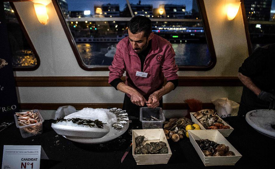 Campeonato francês de abertura de ostras organizado pela Comissão Nacional de Mariscos e Agricultura (Comite nacional de la Conchyliculture) ao longo do Rio Sena em Paris, na França.