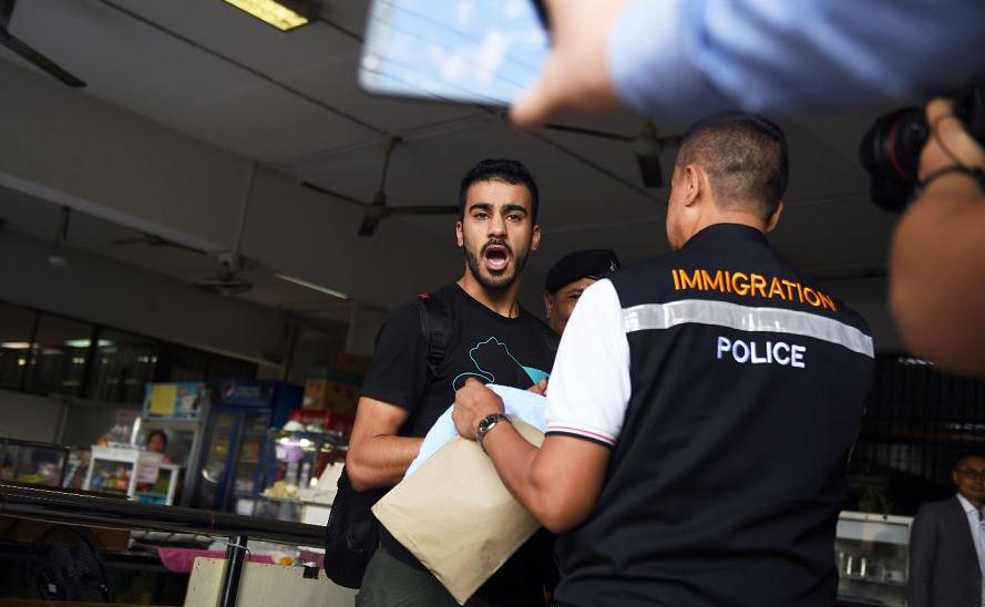 Hakeem Alaraibi (C), um ex-jogador de futebol do time Bahrain, com estatuto de refugiado na Austrália, é escoltado pela polícia de imigração, a um tribunal em Banguecoque, quando em viagem de férias pelo seu país natal.