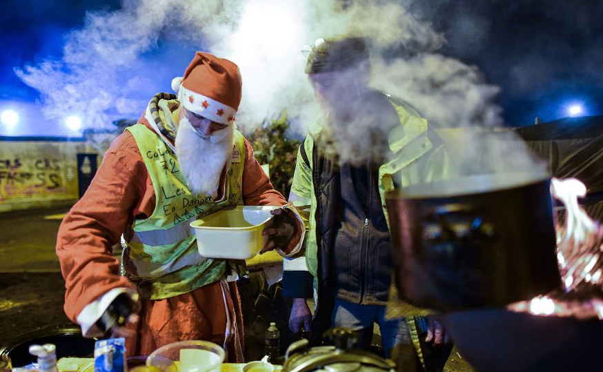 Um homem vestido como Papai Noel toma um café com manifestantes do colete amarelo (Gilet jaune) num bloqueio em um depósito de petróleo perto de Le Mans, no noroeste da França.