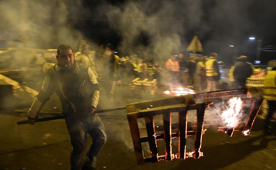 Manifestantes de coletes amarelos (gilets jaunes) queimam barricadas, após o anúncio da intervenção da polícia, ao bloquei do acesso para o depósito de óleo em Le Mans, noroeste da França.