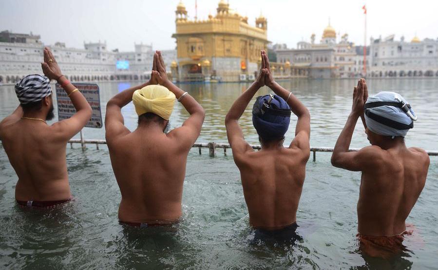 Devotos Sikh mergulham no Santo no sarovar (tanque de água) por ocasião do dia do martírio do 9º  Guru Sikh Guru Shri Guru Teg Bahadur Sahib no Templo Dourado em Amritsa, na Índia.