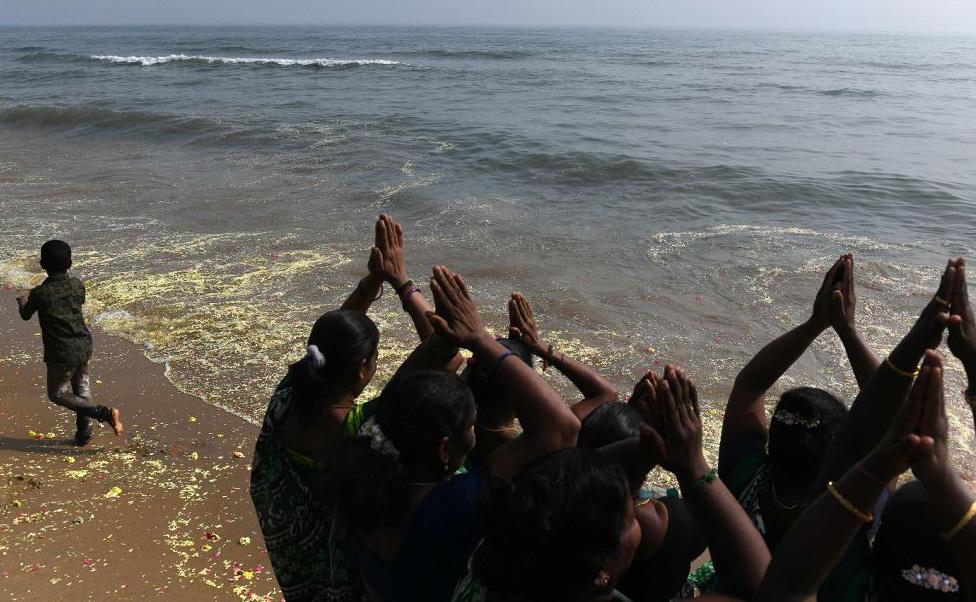 Mulheres fazem orações para as vítimas do tsunami de 2004 na praia de Pattinapakkam em Chennai. O terremoto e o tsunami que atingiu o Oceano Índico em 26 de dezembro de 2004 mataram quase 230.000 pessoas.