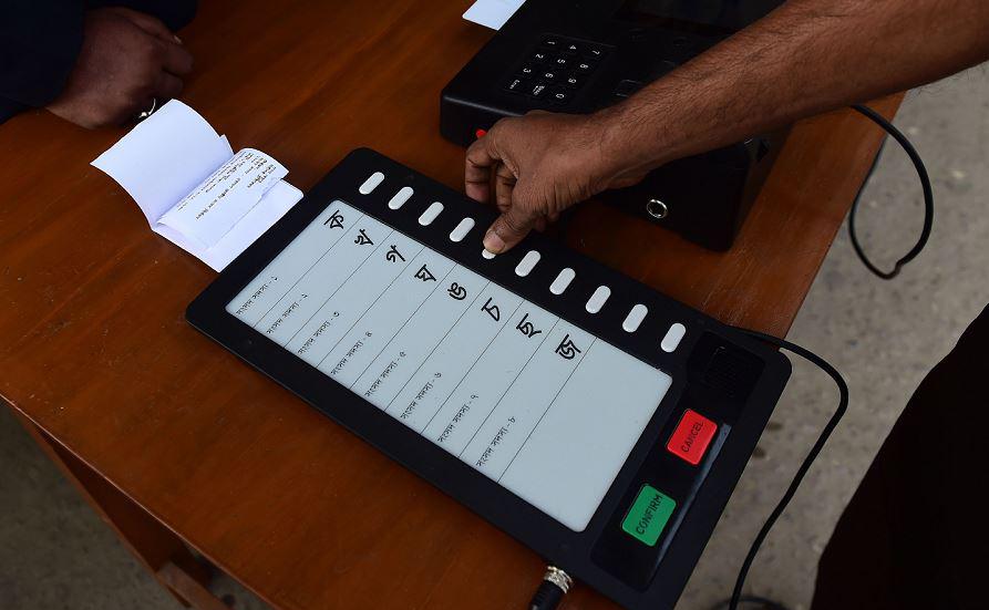 Funcionários da Comissão de eleições um Bangladesh demonstram  como usar uma máquina de votação eletrônica (EVM) em Dhaka.