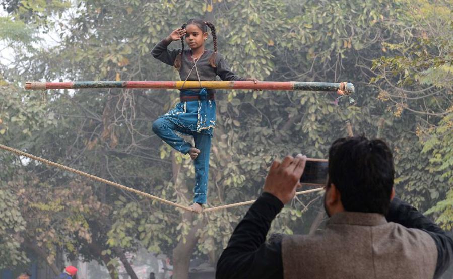 A garota Indiana Laxmi, 10, se equilibra em uma corda durante um show de rua em Amritsar.