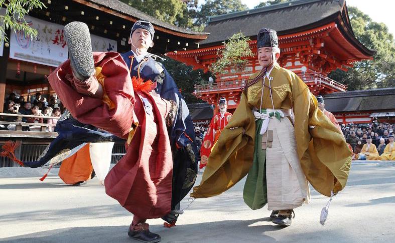 Homens em quimonos tradicionais chutam uma bola de pele de veado durante a cerimônia de Kemari Hajime no santuário de Shimogamo em Kyoto.