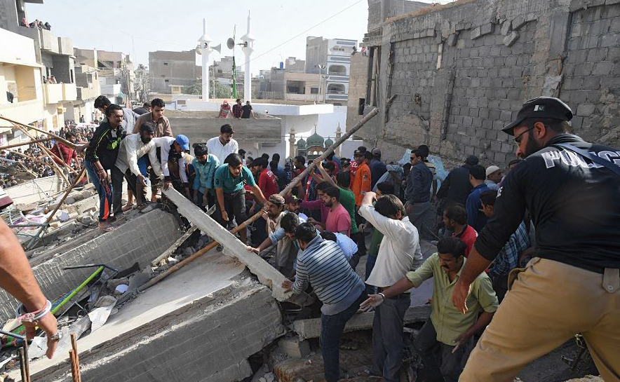 Voluntários paquistaneses procuram vítimas em escombros num edifício de três andares que desabou no bairro de Jaffar Tayar, em Karachi. Pelo menos duas pessoas morreram e outros ficaram feridos.