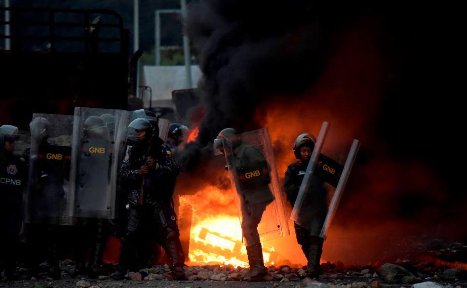 Forças de segurança venezuelana em confronto com os partidários do líder da oposição Juan Guaido na ponte Internacional Francisco de Paula Santander, na fronteira com a Colômbia.