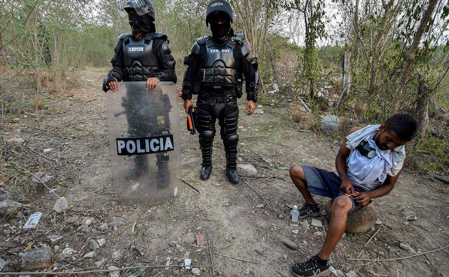 Agentes da polícia colombiana patrulham as margens do Rio Tachira, na fronteira com a Venezuela, à procura de possíveis desertores do exército venezuelano. São cerca de 326 militares que tentam atravessar a fronteira.