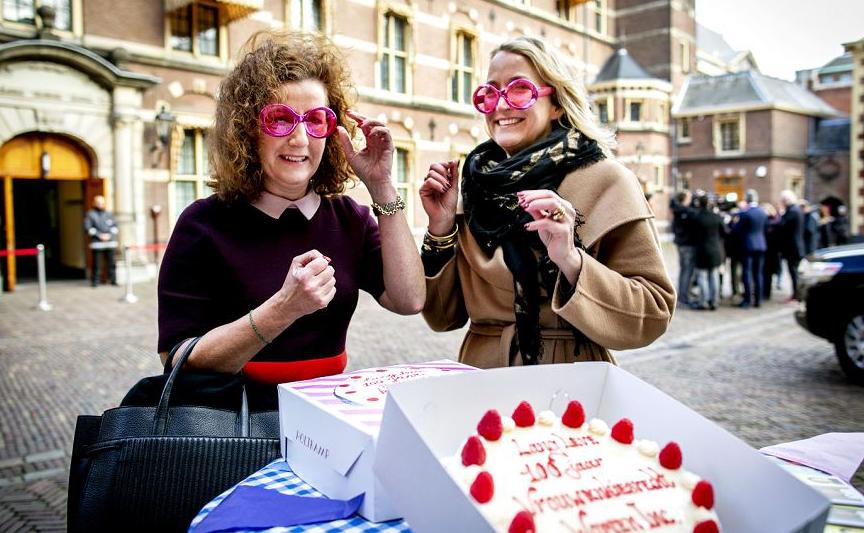 A ministra holandesa da educação Ingrid van Engelshoven (E) usa óculos cor de rosa em frente ao bolo comemorativo em Binnenhof, Haia.