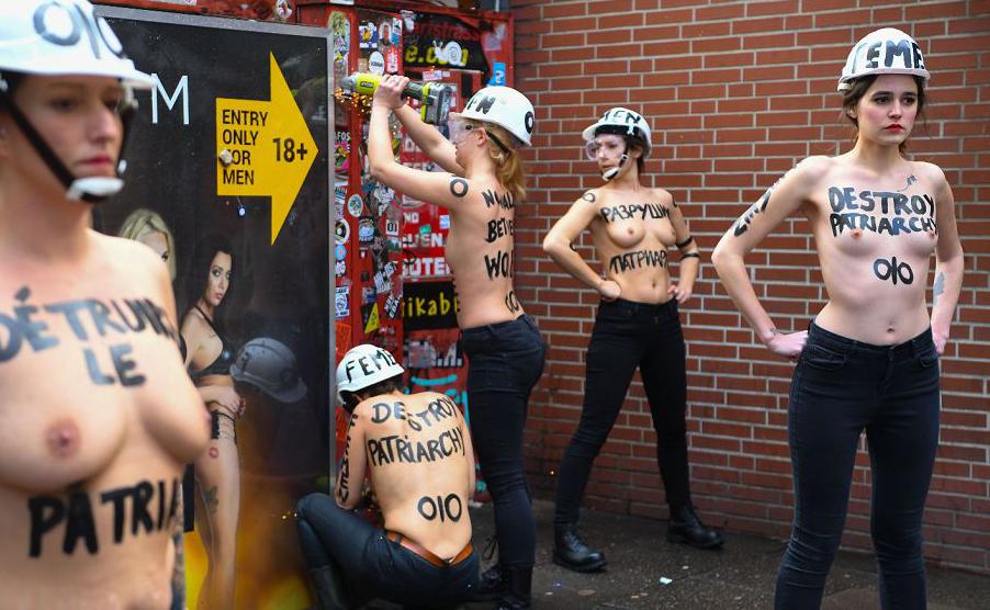 """Ativistas do movimento Femen escreveram """"Destruir o Patriarcado"""" em seus corpos e fazem barricadas impedindo a visão das mulheres expostas em vitrines na Herbertstrasse, uma rua no distrito da luz vermelha em Hamburgo, norte da Alemanha."""