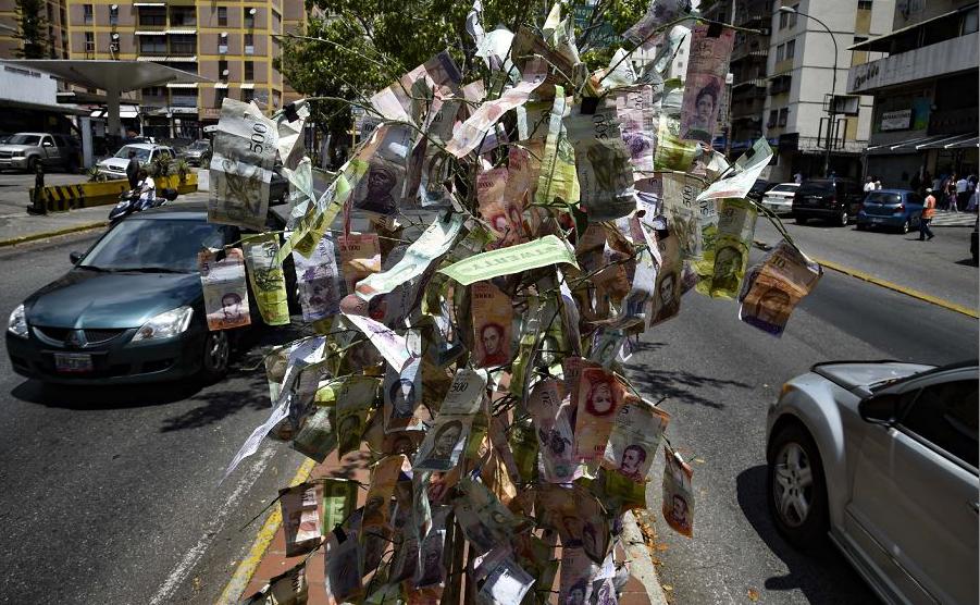 Árvore decorada com as cédulas inúteis dos bolívares venezuelas em Caracas durante uma queda de energia geral no país.