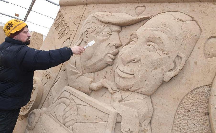 """O polonês Wodek Bludik trabalha em escultura de areia inspirada no grafite do Muro de Berlim """"Beijo de irmãos"""" que está hoje na Galeria Eastside de Berlim. Aqui as figuras de Leonid Brejnev e Erich Honocker foram trocadas por Donald Trump e Vladimi"""
