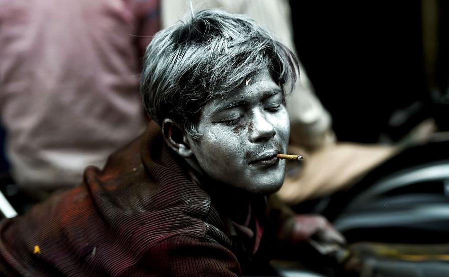 Vendedor indiano de pó colorido se prepara para o início do festival da primavera, Holi, em Nova Deli.