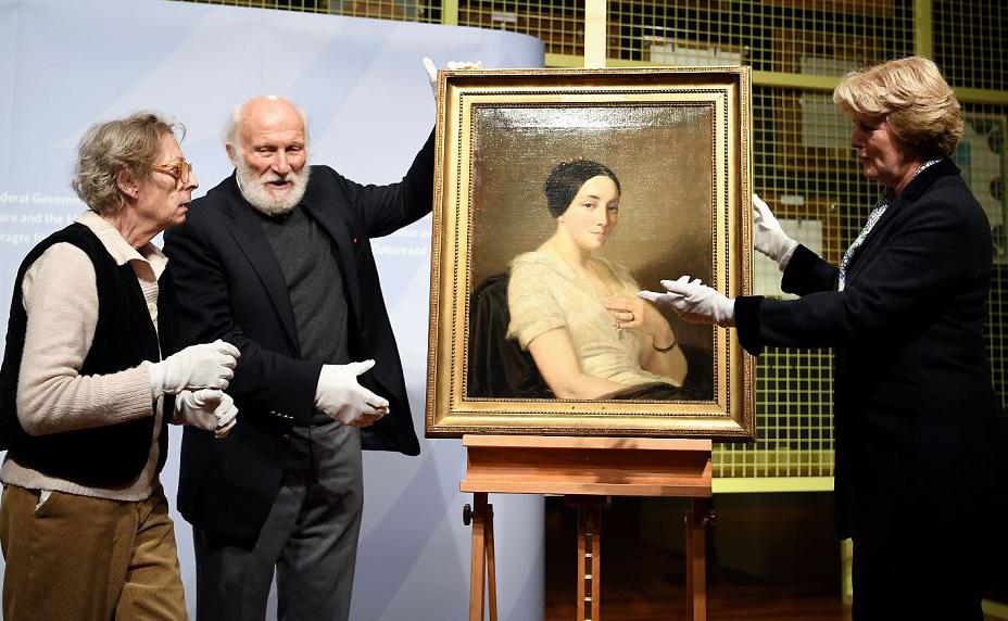 """Os herdeiros Maria de las Mercedes Estrada (E) e Wolfgang Kleinertz (C) entregam ao Comissário do Governo Federal da França Monika Gruetters (D) a pintura saqueada pelos nazistas  intitulada """"retrato de um mulher sentada""""pelo artista Thomas Couture em B"""
