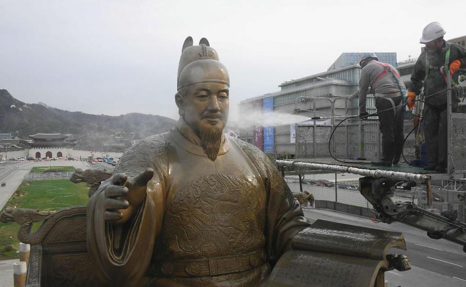 Trabalhadores sul-coreanos limpam a estátua de bronze do Rei Sejong, do século XV, na Praça  Gwanghwamun.