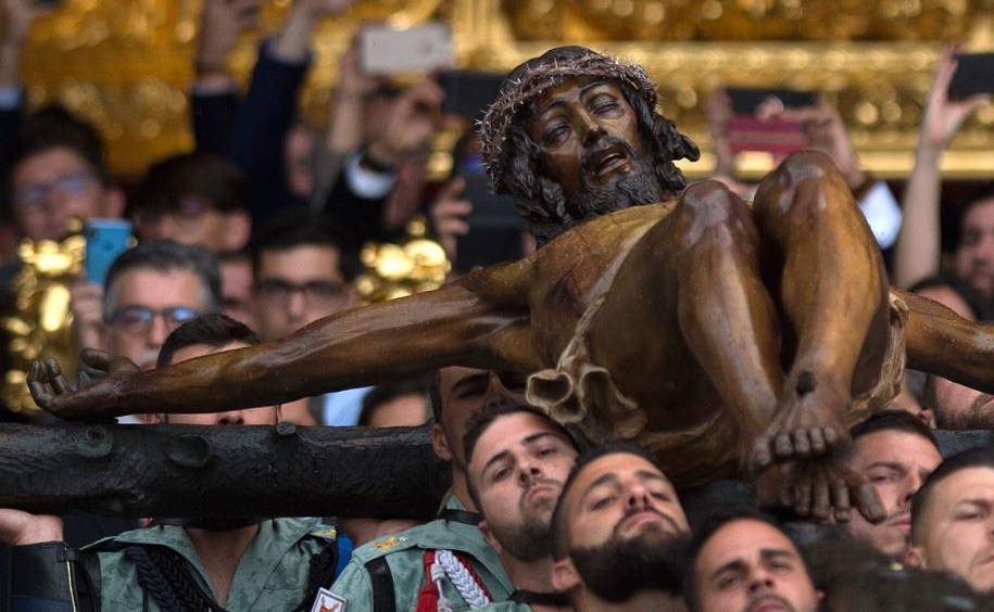 """Membros da Legião Espanhola carregam uma estátua representando """"El Cristo de la Buena Muerte"""" (o Cristo da boa morte) na Igreja de Santo Domingo de Guzman durante a procissão da semana Santa do 'Cristo de Mena' em Málaga, no sul da Espanha."""