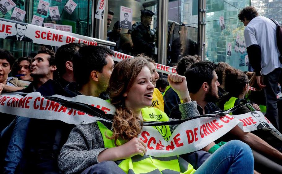 Ativistas de mudança de clima bloqueiam a entrada da sede do banco Societe Generale durante um protesto ambiental em Paris.