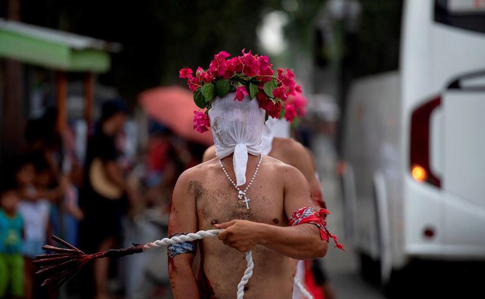 Devotos se mutilam com tiras de bambu em uma rua em San Juan, Pampanga, nas Filipinas, durante a encenação da crucificação de Jesus Cristo na sexta-feira.