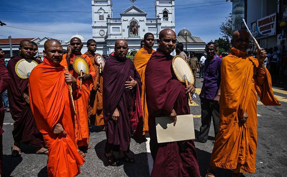 Monges budistas em frente ao Santuário de Santo Antônio em Colombo, um dia depois que a igreja foi atingida por uma série de explosões de bombas que alvejaram igrejas e hotéis de luxo no  Sri Lanka, causando a morte de pelo menos 290 pessoas.