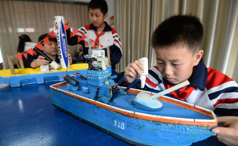 Alunos do ensino fundamental fazem modelos de navio de guerra em Handan no norte da província de Hebei, China para comemorar o 70º aniversário da Fundação do povo chinês.