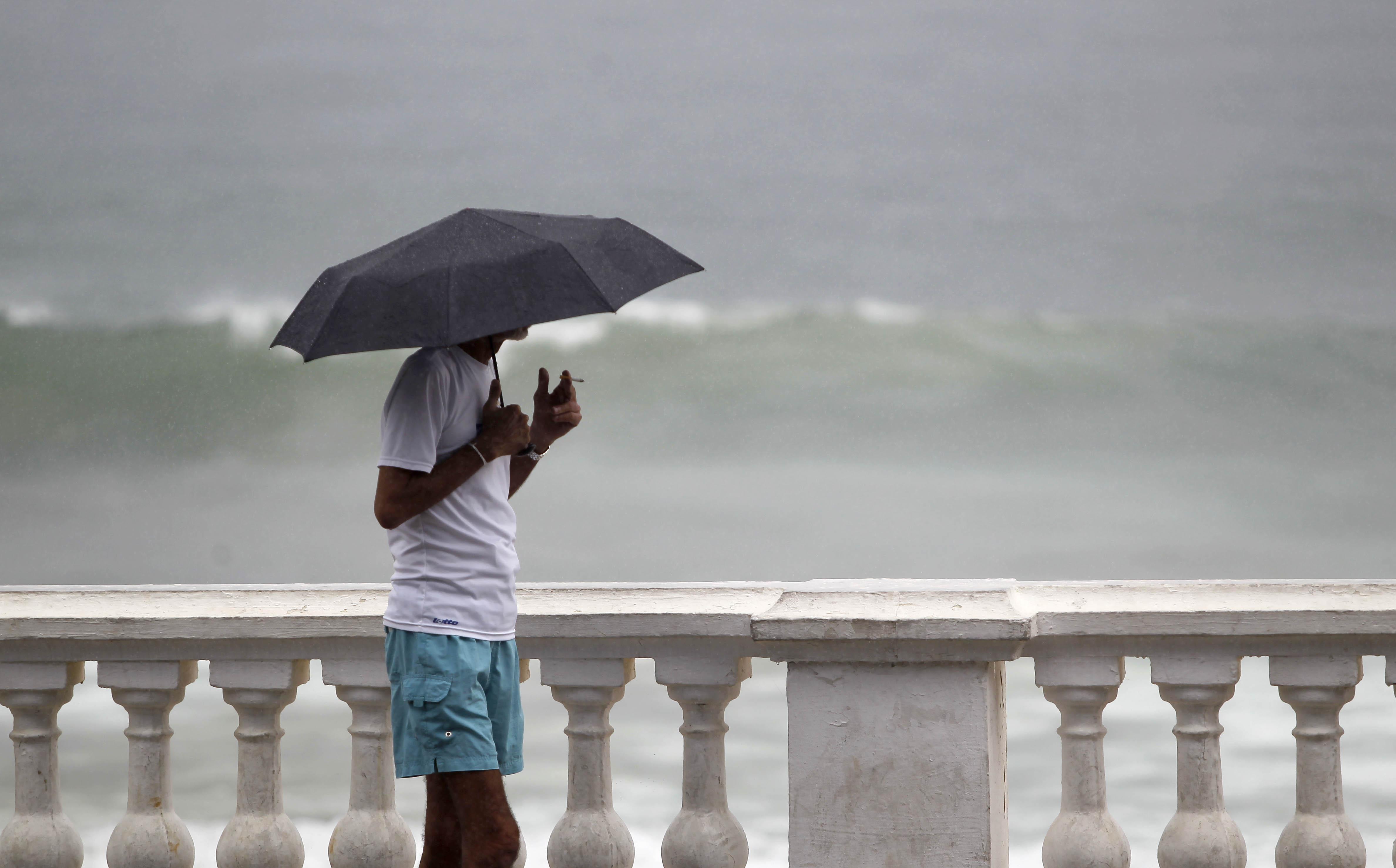 Homem observa o mar da Barra.