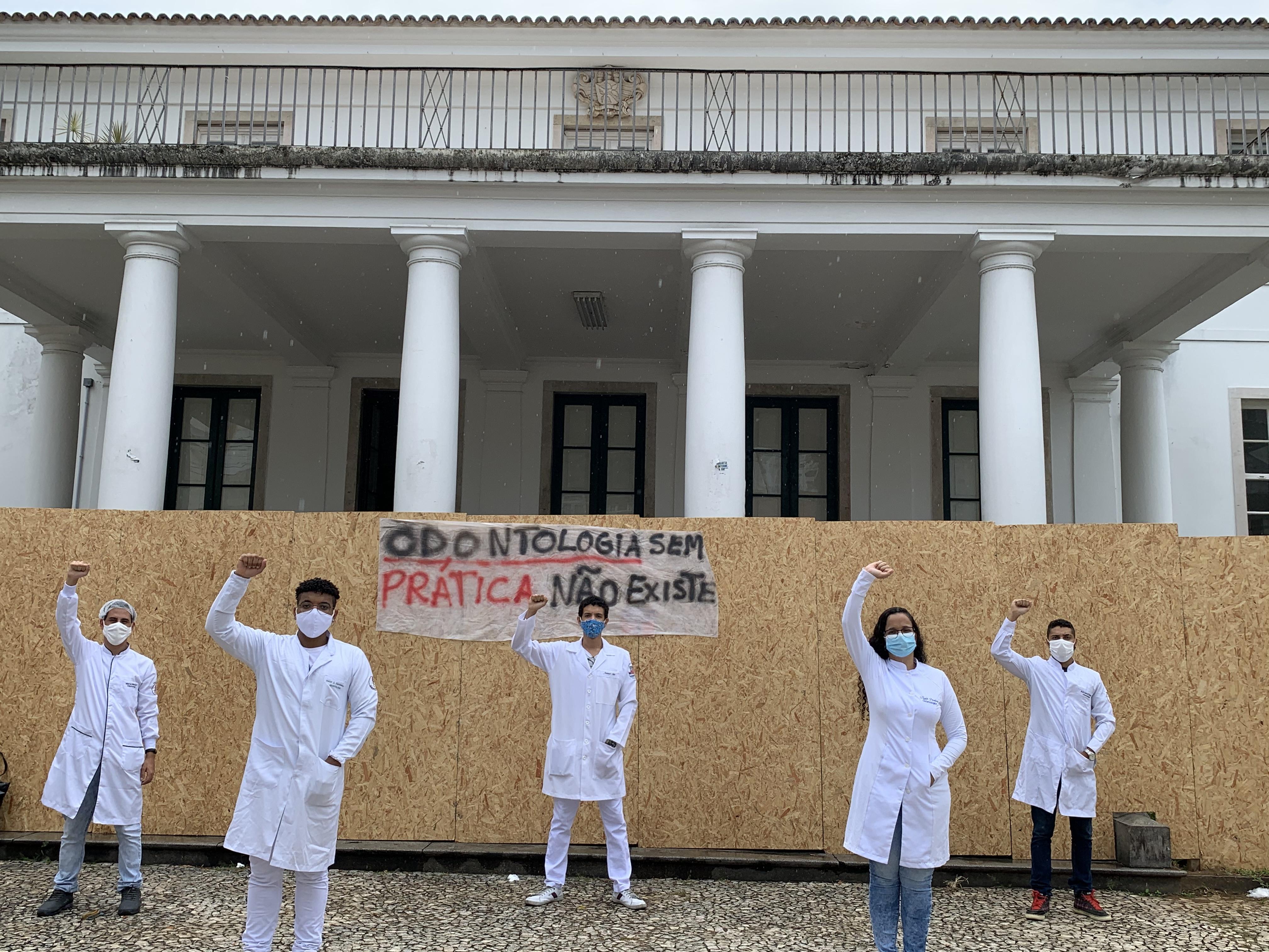 Estudantes posam com punhos para cima em frente ao prédio da Reitoria