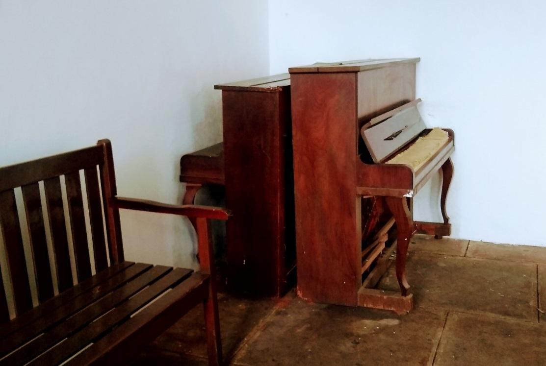 Piano da Pianofatura Paulista, marca da Fritz Dobbert – Não é possível ver muitos detalhes porque piano está encostado a uma parede, mas há um entalhe com data de outubro de 1967